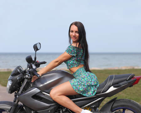 young girl on a motorcycle in the summer by the sea