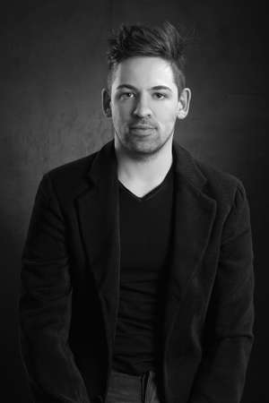 young stylish solid man in a blazer against a dark background