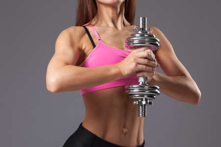 young athletic muscular female body on gray background