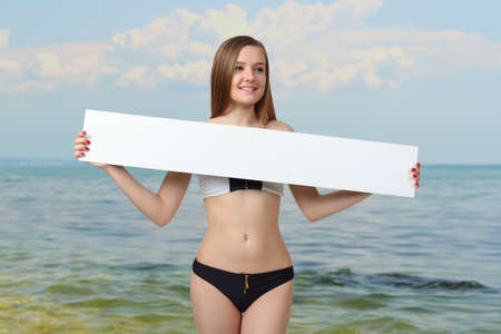 Sexy young woman posing in bikini showing blank placard board, isolated on white background