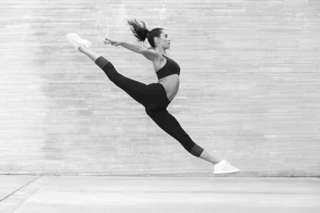 young athletic flexible girl in a jump on a gray background 写真素材