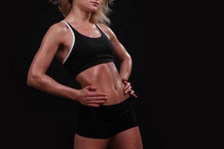 mujer joven fitness sobre un fondo oscuro