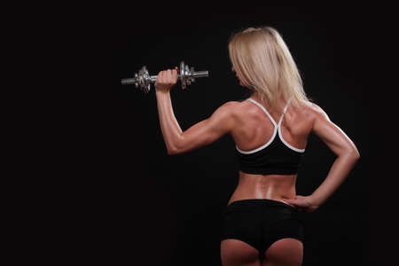 Nice sexy woman doing workout with dumbbell on a darck background