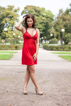 young sexy girl in red dress posing in the park Stockfoto