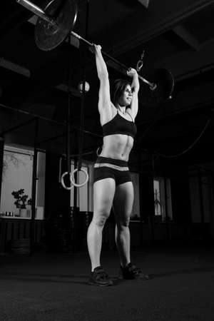 strong Woman lifting heavy barbell in gym