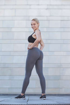 Fitness young sporty woman showing her well trained body