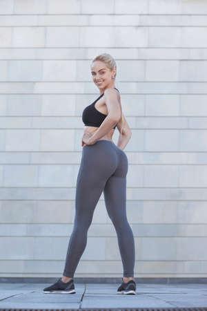 Junge sportliche Frau der Eignung, die ihren gut trainierten Körper zeigt Standard-Bild