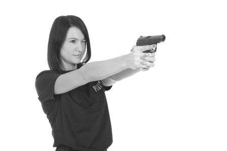Joven policía con pistola sobre un fondo blanco. Foto de archivo