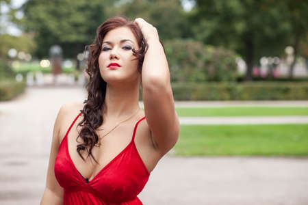 young girl in red dress posing in the park