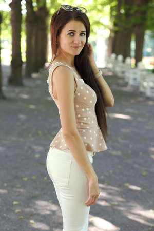 Happy young woman in white pants and shirt