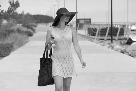 young woman with bag and head walks down the street