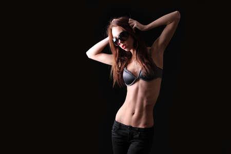young slim girl with a thin belly on a black background Zdjęcie Seryjne