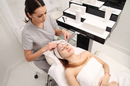 Young Woman having cosmetic facial seaweed treatment in spa.