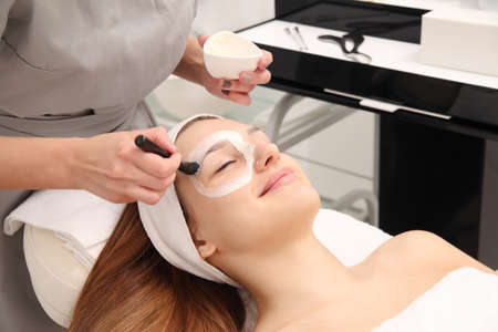Young Woman having cosmetic facial seaweed treatment in spa. Stock Photo - 133742309