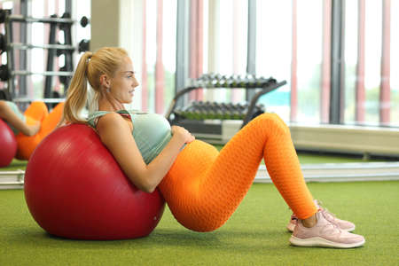 Smiling Young Pregnant Woman Exercising With Pilates