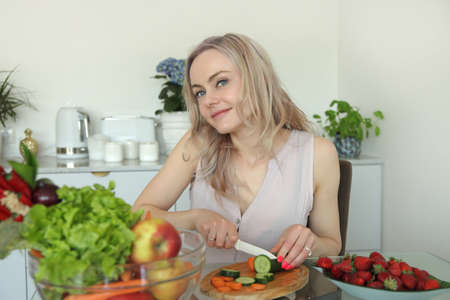 beauty young positive smiling woman with vegetables in the kitchen