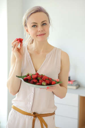 young positive smiling woman with a plate of strawberries at home Stock Photo