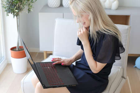 Young Blond Woman Using Laptop in Home