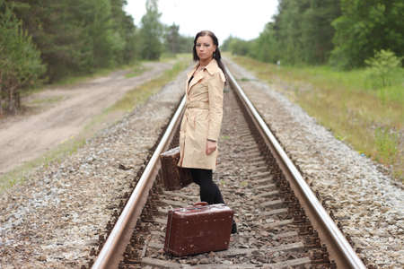 Woman with a suitcase on the rails