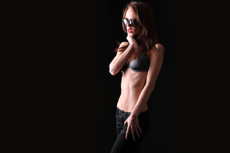 young slim girl with a thin belly on a black background Imagens