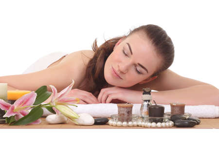Young woman laying on massage table with candles