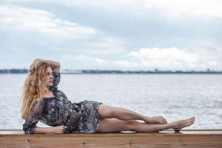 gelukkig meisje in een jurk aan zee Stockfoto
