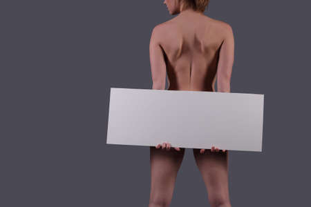 nude woman holding blank banner on dark background