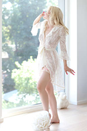 young beautiful blonde in a transparent dressing gown Zdjęcie Seryjne