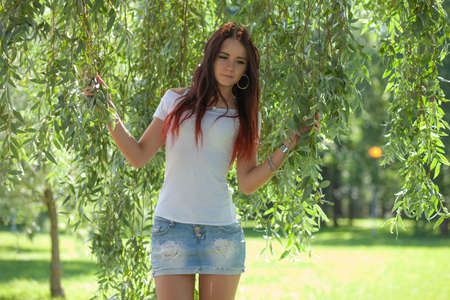Sexy girl with mini skirt on green grass Imagens