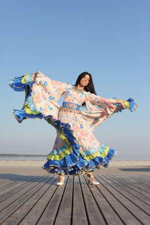young beautiful woman dancing in gypsy dress