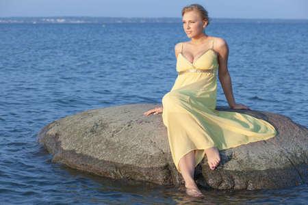 young beautiful girl on a stone in the sea 免版税图像