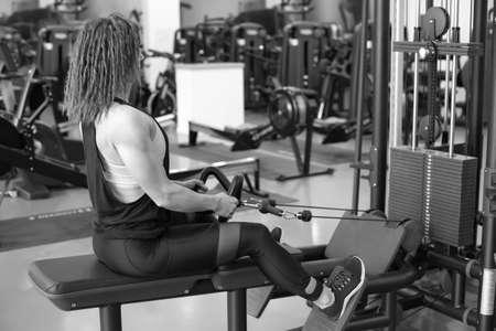 Sexy jeune fille athlétique travaillant dans la salle de gym.