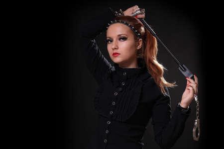 Mädchen in Schwarz mit Handschellen Peitsche auf schwarzem Hintergrund