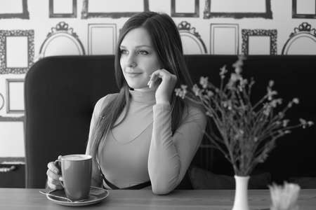 Girl in cafeteria with a mug of tea or coffee Banco de Imagens