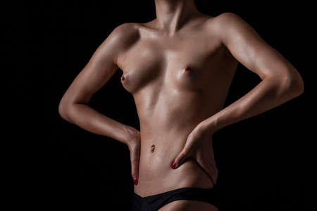 Nude body of the beautiful girl over dark background