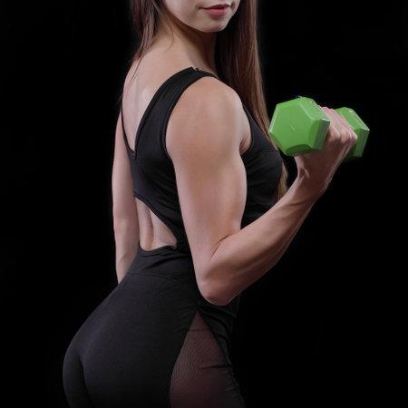 Beautiful fitness woman lifting dumbbells on a black background 版權商用圖片