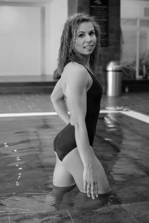 Young smiling athletic girl in a blue swimsuit in the pool