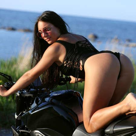 fashion portrait of pretty young woman in bikini on a motorcycle Stok Fotoğraf