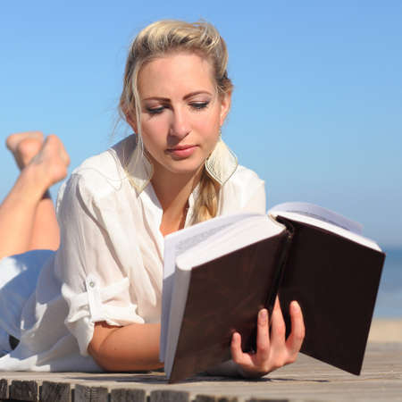 young Woman reads a book on the beach Stock Photo
