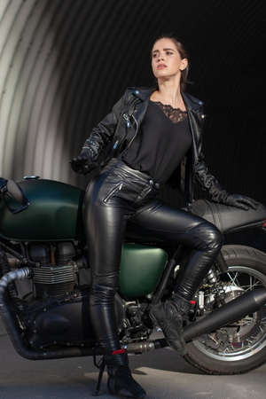 young beautiful woman in black with a motorcycle Reklamní fotografie
