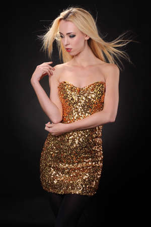 young woman in a shiny dress on a black background