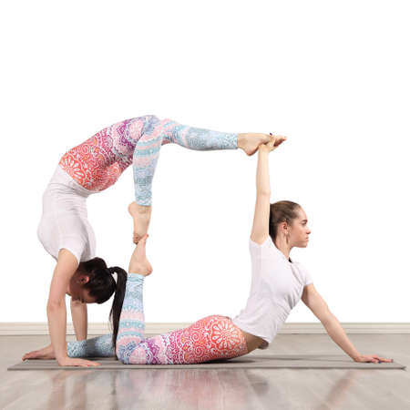 Two slim woman are doing yoga indoors