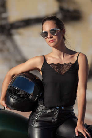 young beautiful woman in black with a motorcycle 版權商用圖片