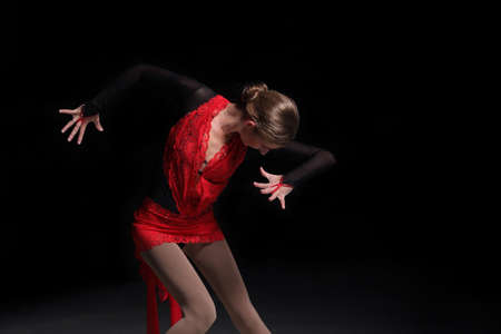 young woman figure skater on a dark background 스톡 콘텐츠