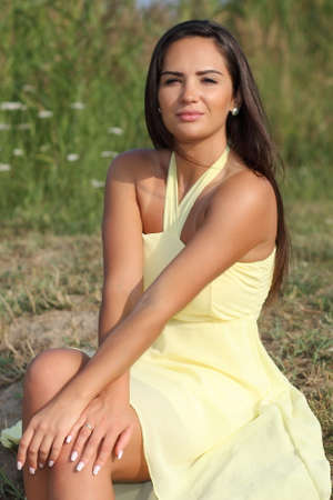 young beautiful woman in yellow dress posing in summer