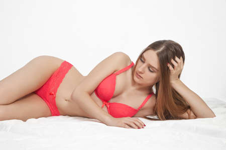 Young cute woman in sexy lingerie on a light background