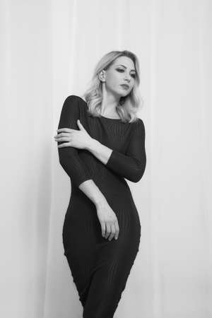 slender young woman in a black sexy dress