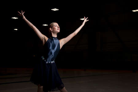 young woman figure skater on a dark background
