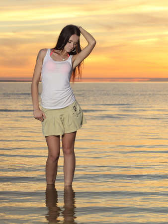 young slim girl in a dress posing at sunset on the sea