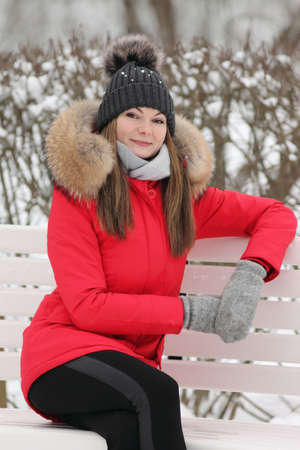 young woman in a red jacket in winter on a background of snow